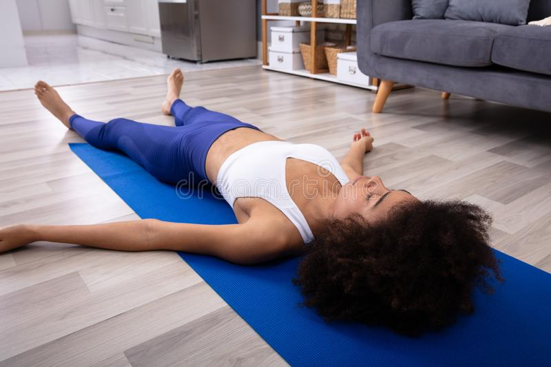 Woman Lying On Blue Yoga Mat royalty free stock images