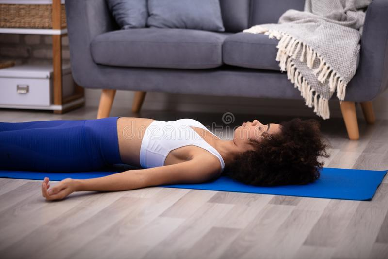 Woman Lying On Blue Yoga Mat stock image