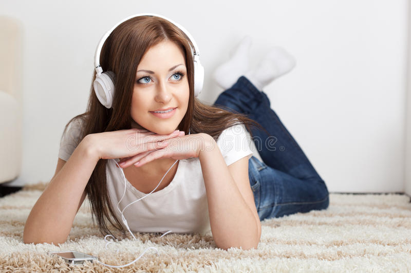 Woman Lying On Carpet And Listen To The Music Stock Image