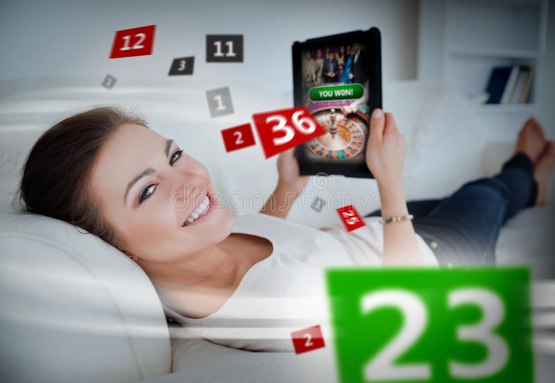 Woman lying on couch and gambling on tablet stock images
