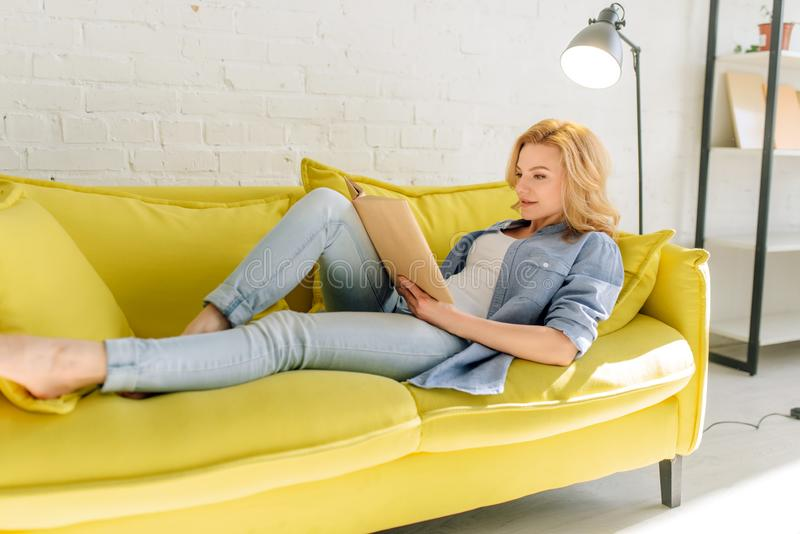 Woman lying on cozy yellow couch and reading book royalty free stock image