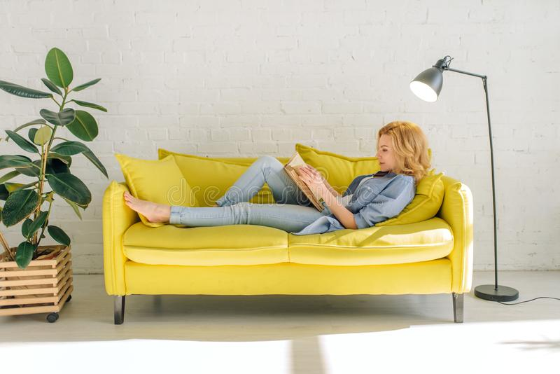 Woman lying on cozy yellow couch and reading book stock photo