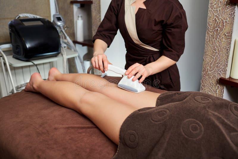 A woman lying down doing cryolipolysis treatment. royalty free stock photo