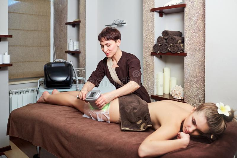 A woman lying down doing cryolipolysis treatment. stock photography