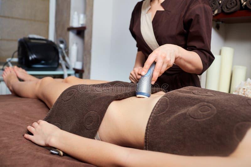 A woman lying down doing cryolipolysis treatment. stock image