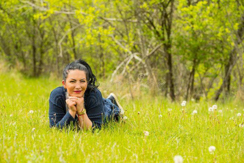 Woman lying down on grass. Beauty woman lying down on grass in nature stock photography