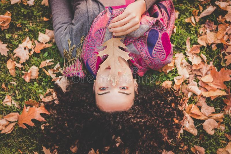 Woman Lying Down On Green Grass Field Holding Brown Leaf stock images