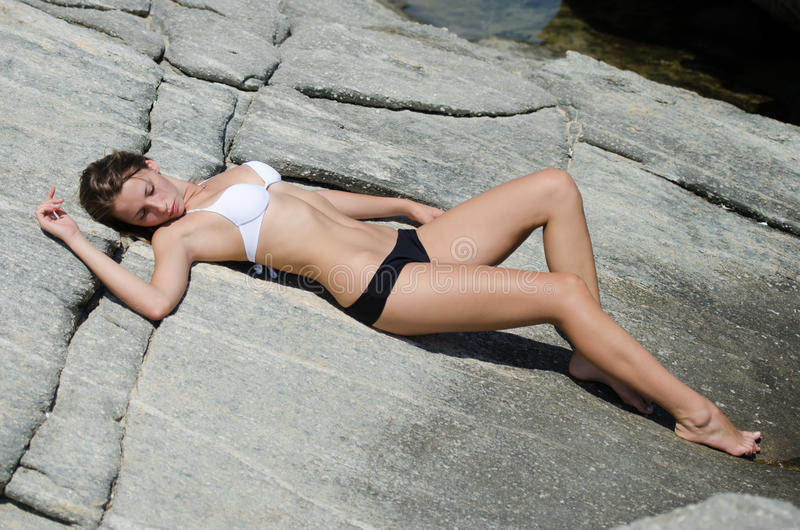 Woman is lying down and sunbathing on solid rocks. Whilst wearing a black white bikini. Full length and horizontal photo royalty free stock photo