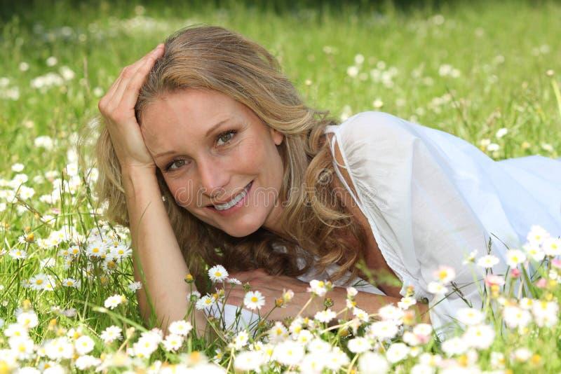 Woman lying in a field stock image