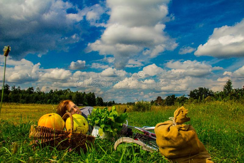 A woman is lying in a field near a pumpkin crop. Autumn landscape. Harvesting. Background stock images