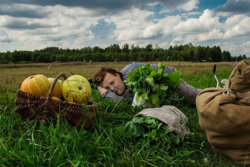 A woman is lying in a field near a pumpkin crop. Autumn landscape. Harvesting. Background stock image