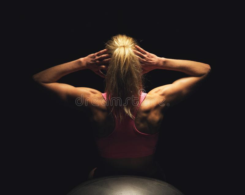Woman Lying on Fitness Ball and Doing Sit Ups stock photo