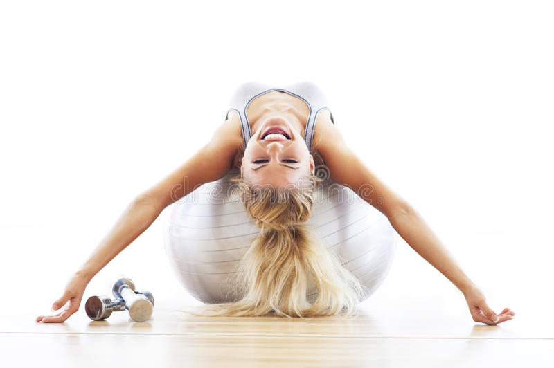 Woman lying on fitness ball. Young woman exercising on a fitness ball royalty free stock photos