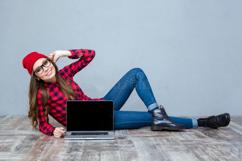Woman lying on the floor and showing blank laptop screen. Portrait of a smiling hipster woman lying on the floor and showing blank laptop computer screen on gray royalty free stock photography