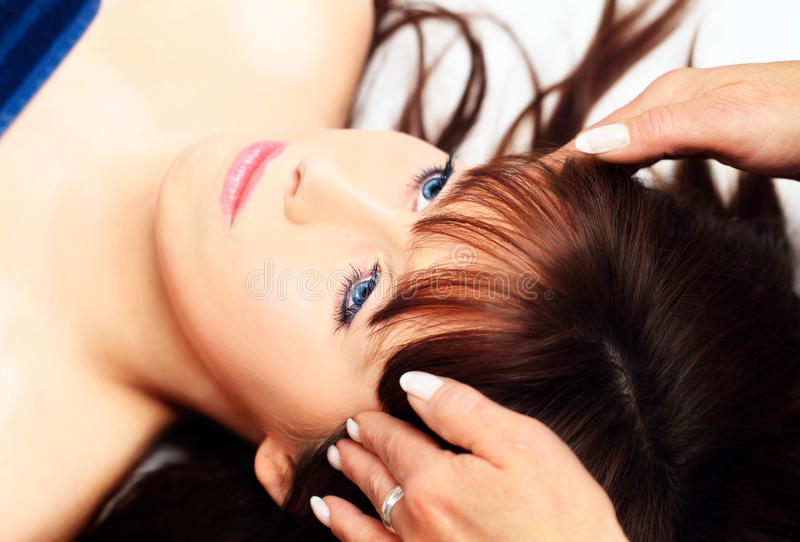 Woman lying, gets massage on her head stock photography