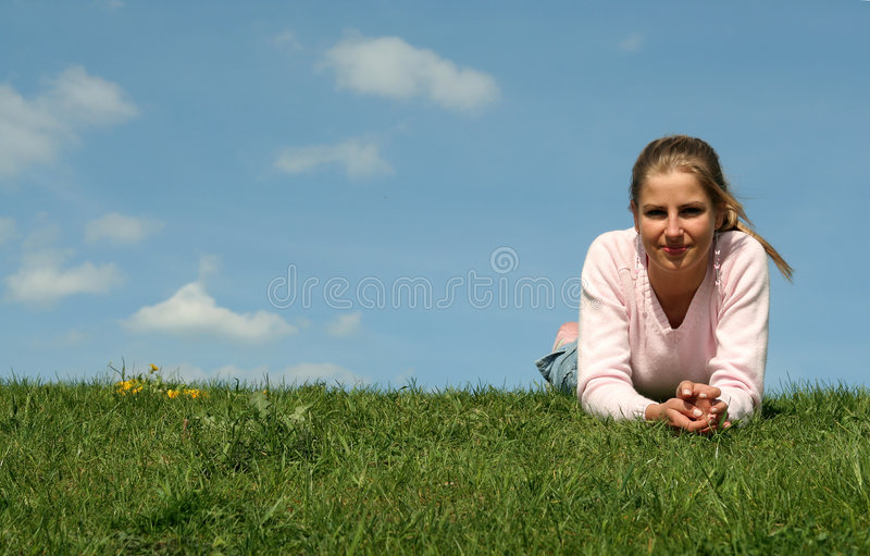 Woman lying on grass royalty free stock photography