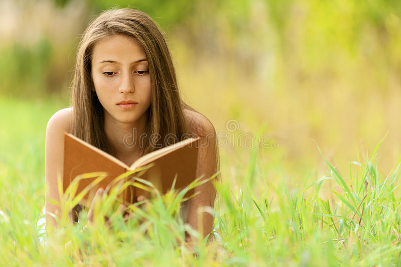 Woman Lying On Grass Reading Book Royalty Free Stock Image