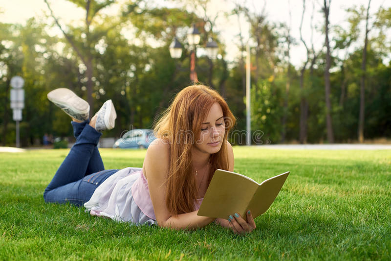 Woman lying on the grass and teaches lessons stock images