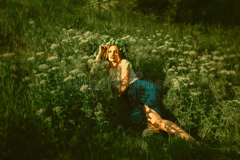 Woman lying in the grass with wreath on head royalty free stock photo