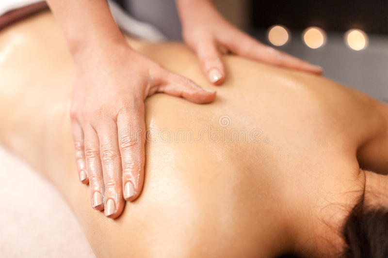 Woman lying and having back massage at spa. People, beauty, healthy lifestyle and relaxation concept - beautiful young woman lying and having back massage at spa