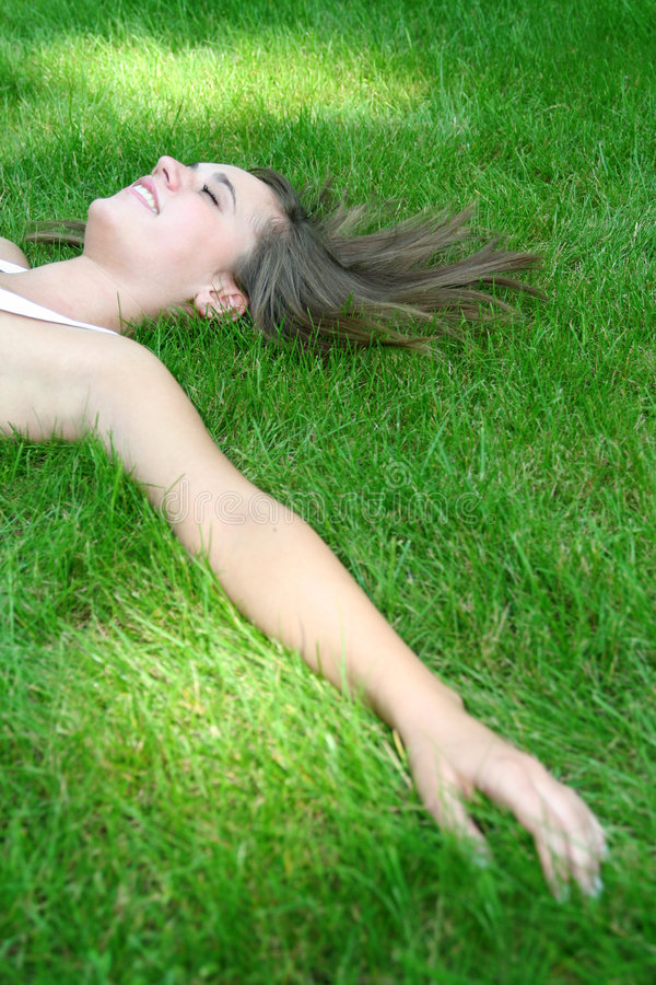Woman lying on a lawn royalty free stock image
