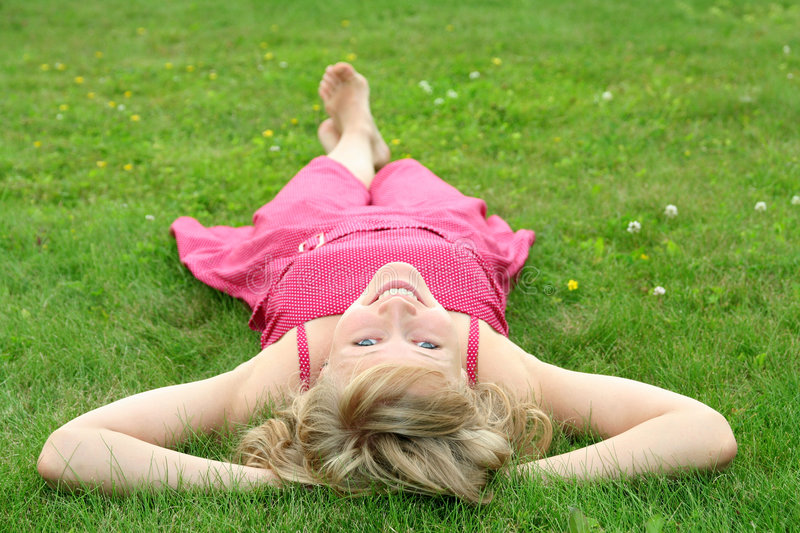 Woman lying on a lawn stock image