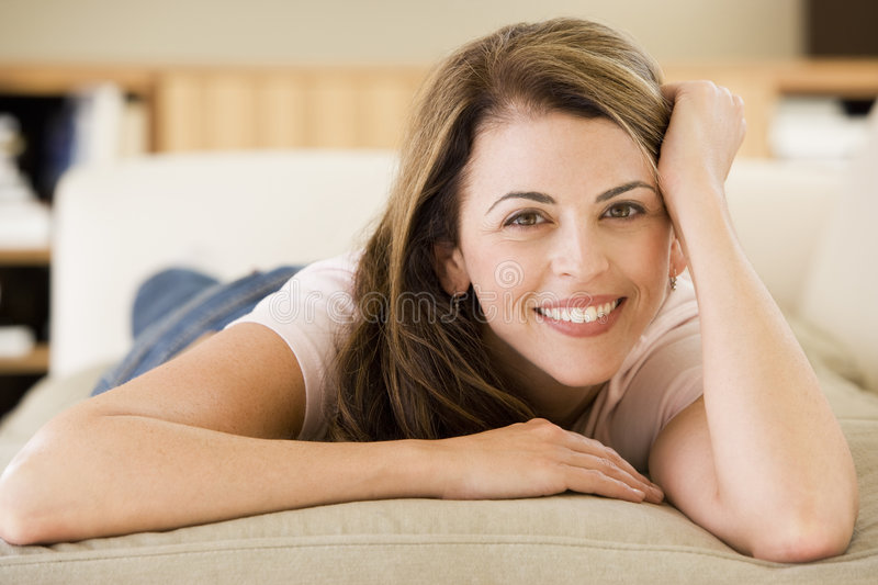 Woman lying in living room stock photos
