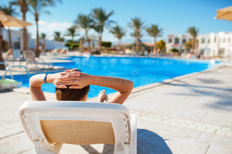 Woman lying on a a lounger and looking the pool royalty free stock photo