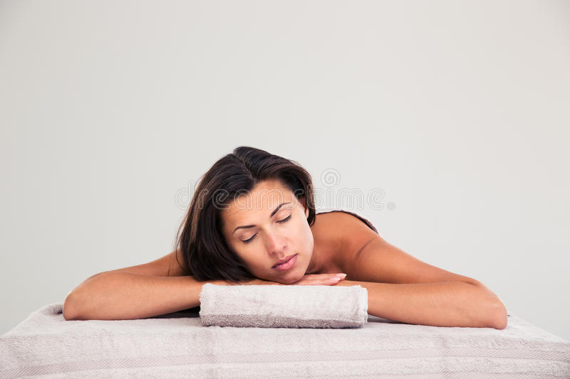Woman lying on massage lounger in a wellness center. Relaxed woman lying on massage lounger in a wellness center isolated on a white background stock photography