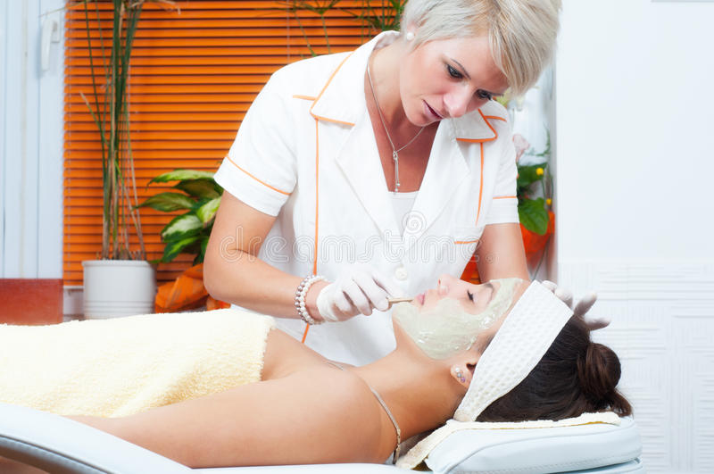 Woman lying on massage table while natural facial mask is put on her face stock images