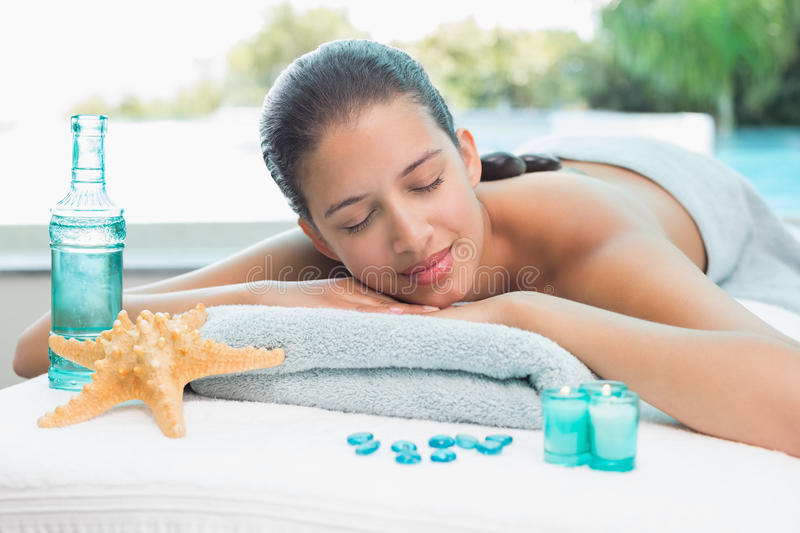 Woman lying on massage table at spa center. Beautiful young woman lying on massage table at spa center stock image