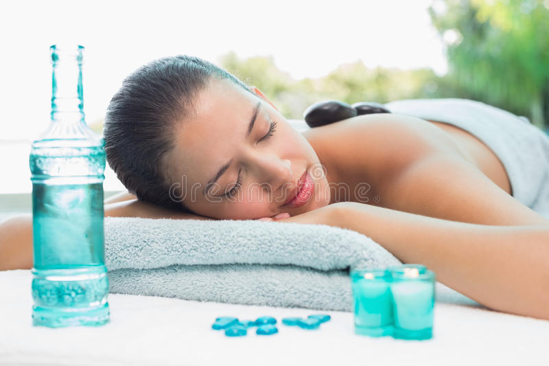 Woman lying on massage table at spa center. Beautiful young woman lying on massage table at spa center royalty free stock photos