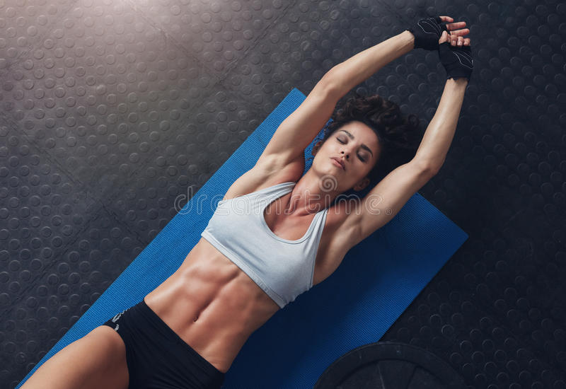 Woman lying on mat doing stretching exercise. Top view of woman lying on mat doing stretching exercise. Fitness woman exercising on yoga mat at gym royalty free stock image