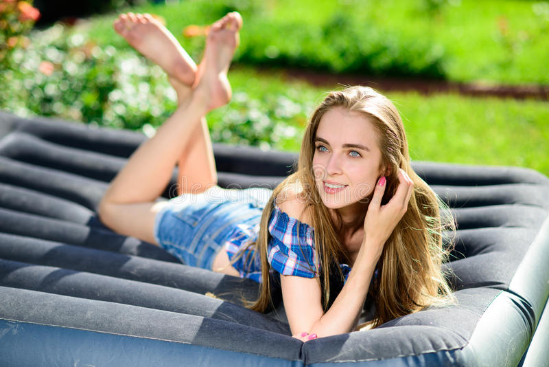 Woman lying on the mattress in the garden royalty free stock photography