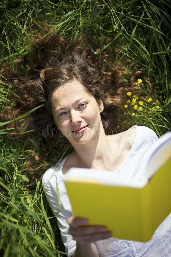 Woman lying in meadow reading royalty free stock photos