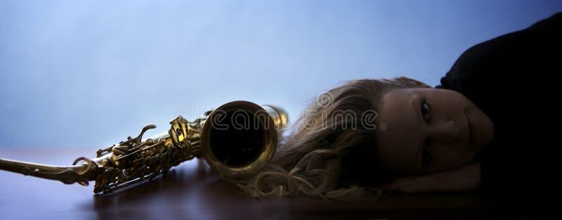 Woman lying next to saxophone stock photos