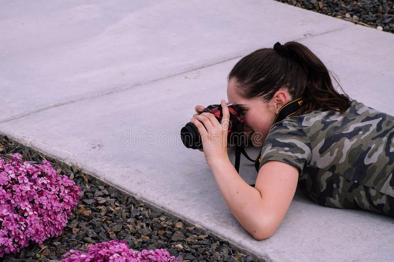 Woman Lying on Pavement While Taking Photo royalty free stock photography