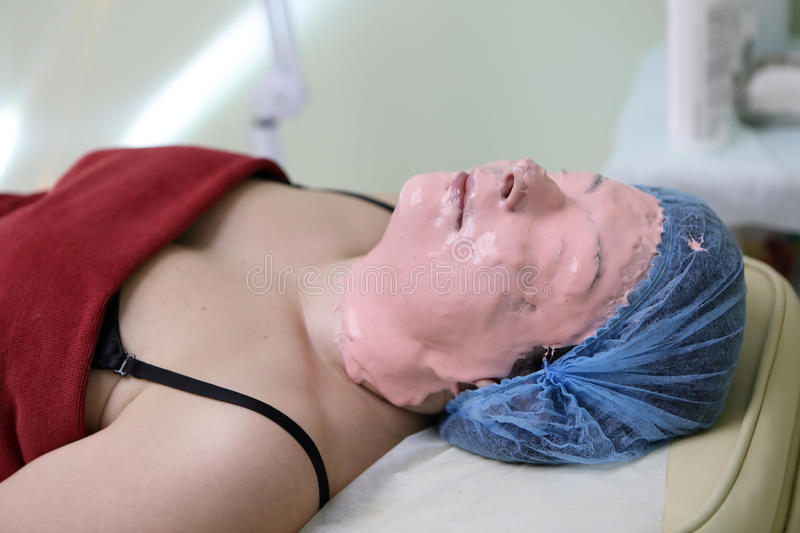 Woman lying with peel off face mask. On her fase royalty free stock photos