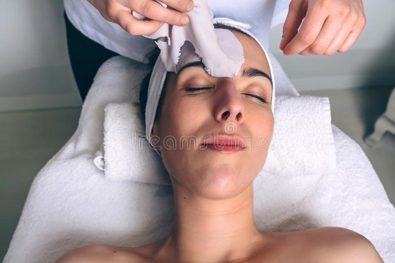 Woman lying while removing facial mask treatment in spa stock photos