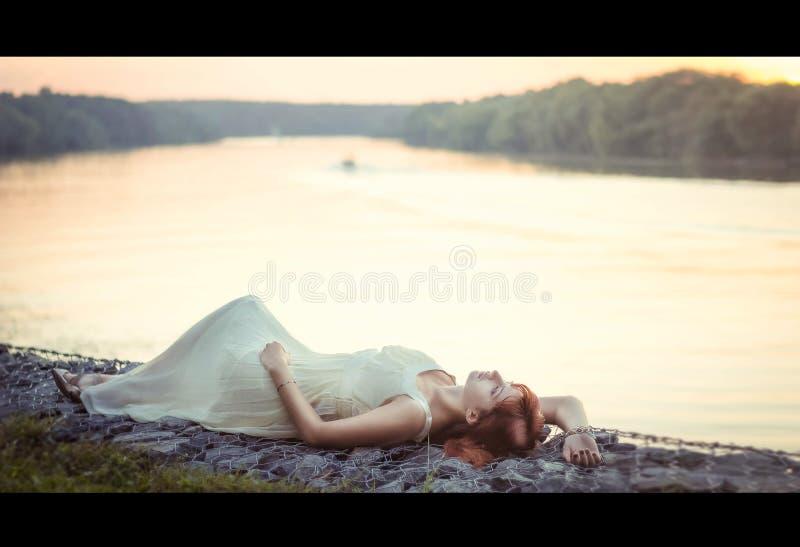 Woman lying on shore stock image