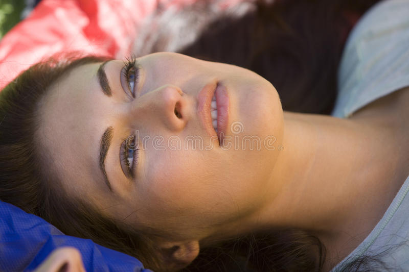 Woman lying on sleeping bag, daydreaming, side view, close-up stock photography
