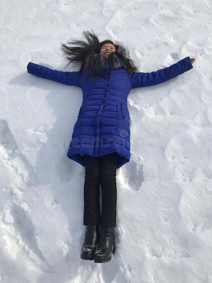 Woman lying on snow. High angle view of happy woman lying on snow and moving her arms and legs up and down creating a snow angel figure royalty free stock images