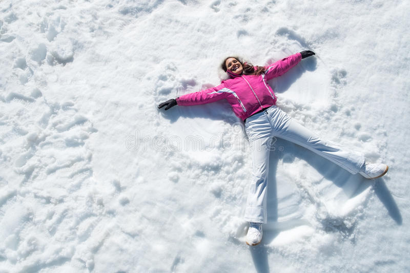 Woman lying on snow. High angle view of happy woman lying on snow and moving her arms and legs up and down creating a snow angel figure. Smiling woman lying on stock photo