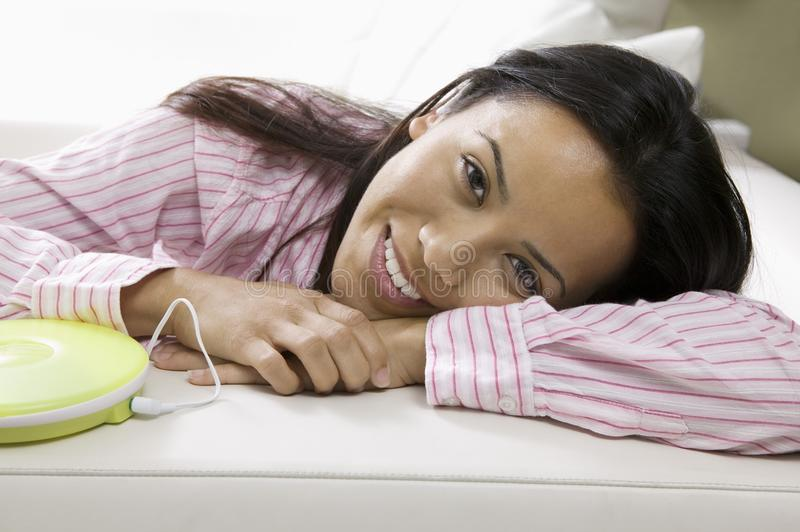 Woman Lying on sofa listening to music