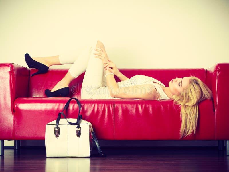 Woman lying on sofa presenting white bag stock image