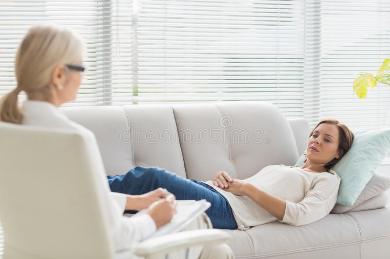 Woman lying on sofa while talking to therapist royalty free stock photography