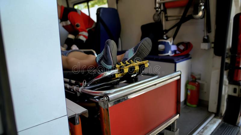 Woman lying on stretcher in ambulance, paramedic examining patient, first aid. Stock photo stock photos