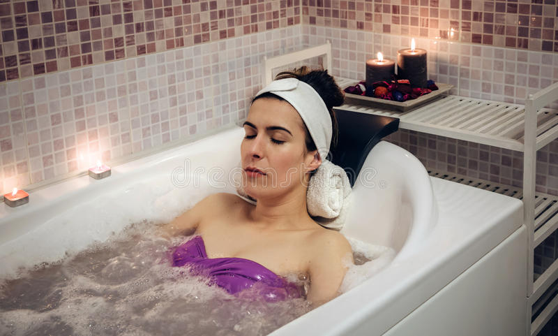 Woman lying in tub doing hydrotherapy treatment stock photography