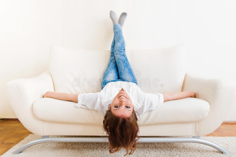 Woman lying upside down on a sofa royalty free stock photos