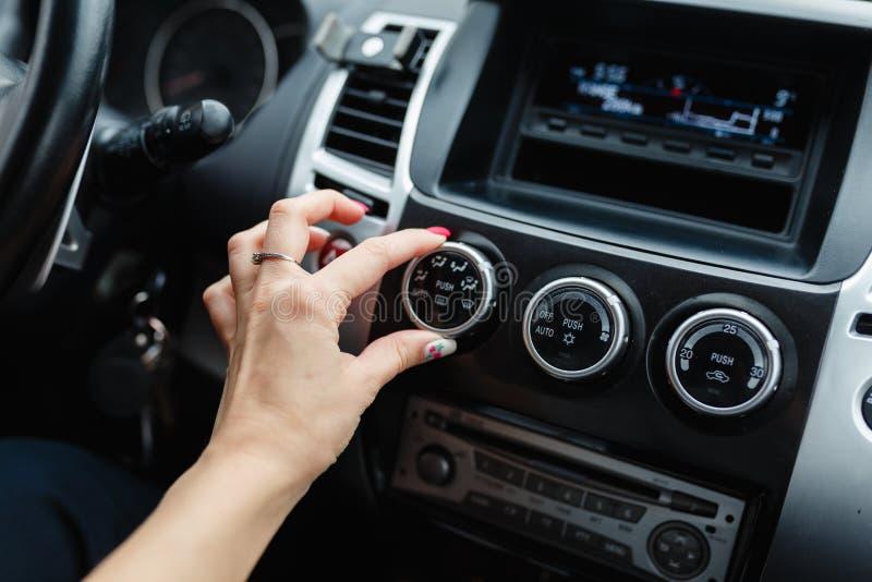 Woman& x27; a mão de s comuta o condicionamento de ar no carro imagem de stock